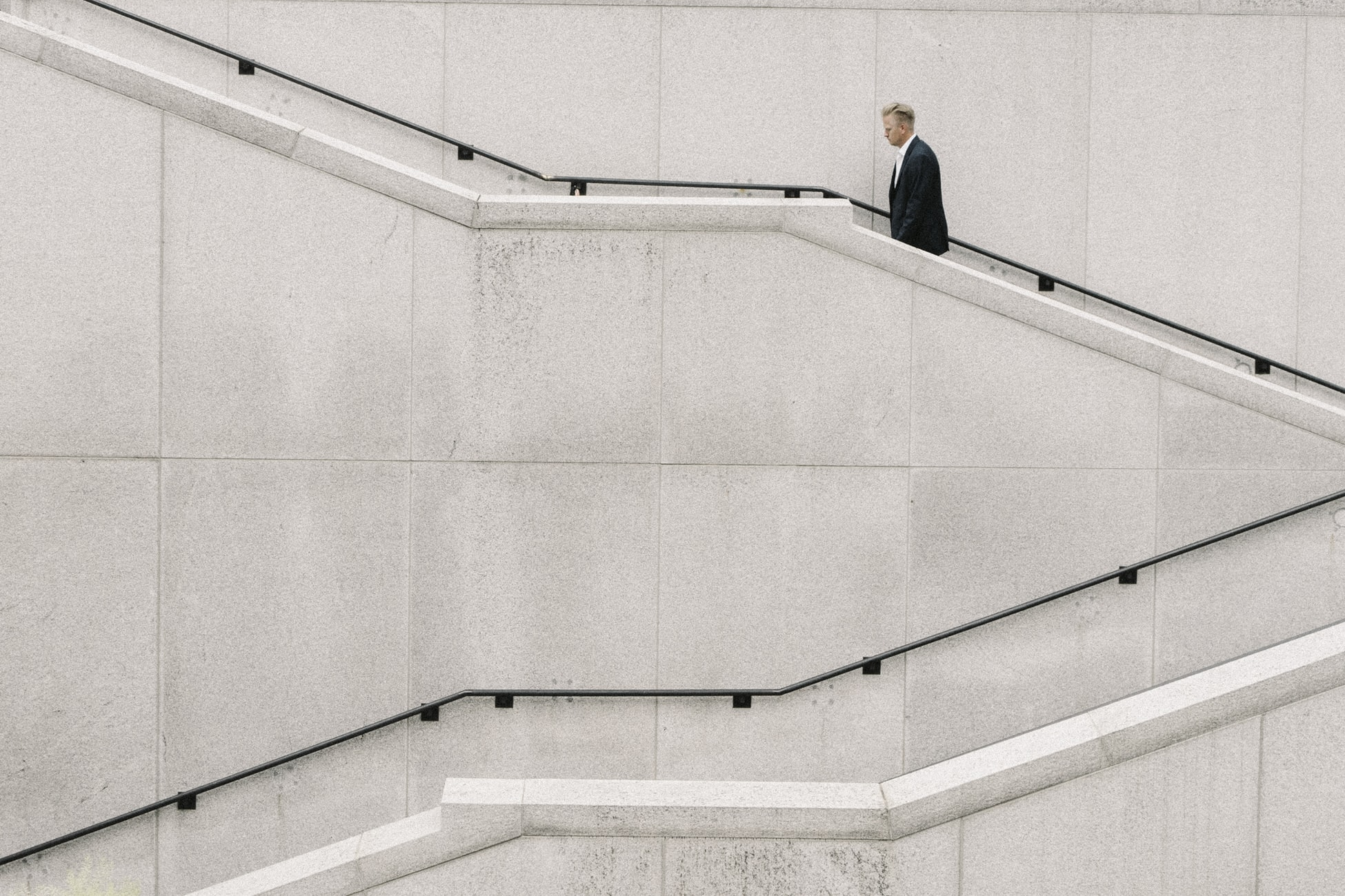 Man in black suit climbing concrete stairs