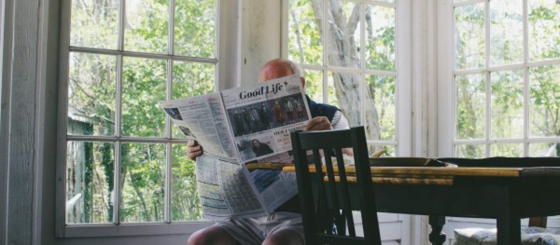 Older man reading the good life paper in shorts at a table - Business Exit Planning Minnesota