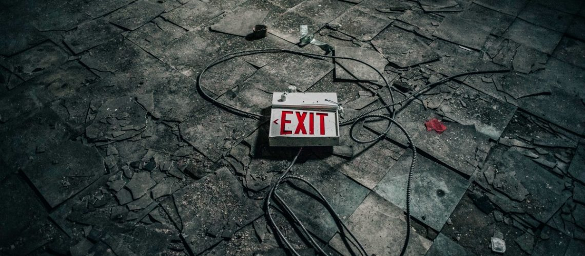 Exit sign unplugged on a dark gray floor