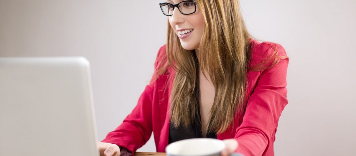 woman with glasses at a desk with coffee and a laptop